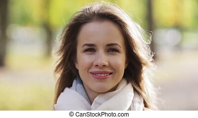 beautiful happy young woman smiling in autumn park - season,...