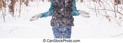 Season, leisure and people concept - close up of woman is happy and throwing snow in the winter nature