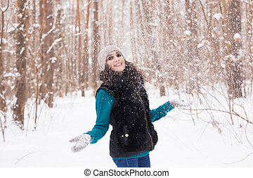 Season, leisure and people concept - young woman is happy and throwing snow in the winter nature