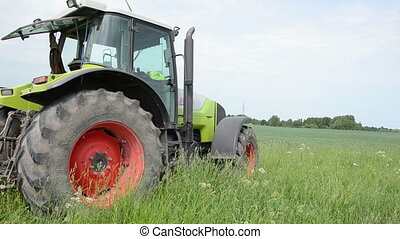 season of field work heavy equipment tractor stands in a meadow