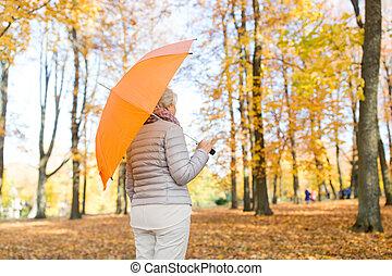 senior woman with umbrella at autumn park