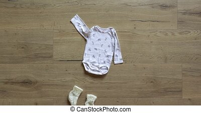 Seasonal baby girl clothes stop motion animation on wooden background. Cute winter Outfit