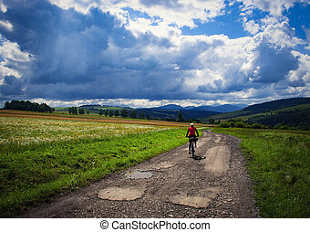 cyclist going through the foothill summer country