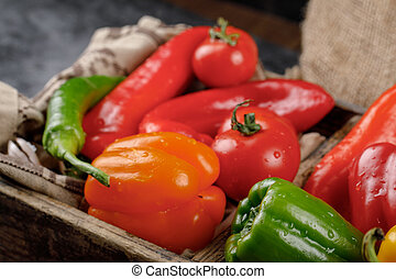 Seasonal peppers in a rustic tray. Top view.
