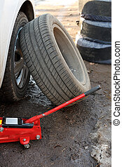 seasonal replacement of tires with jack outdoors - car tire fitting