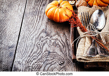 Seasonal table setting with small pumpkins and autumn...
