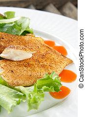Seasoned flaky white fish on a salad