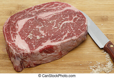 Wagyu ribeye steak on a chopping board being seasoned with sea salt.