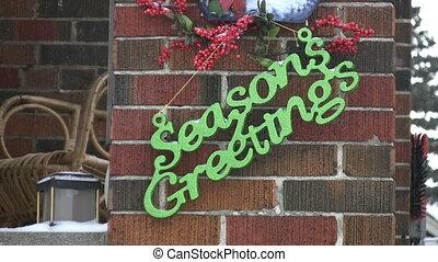 Green %u201CSeasons Greetings%u201D sign on house. Snow falling. Christmas in Toronto, Ontario, Canada.