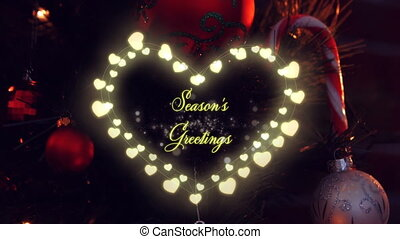 Animation of the words Seasons Greetings in yellow letters and in a heart frame of glowing heart shaped fairy lights with Christmas tree in the background