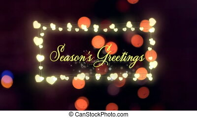 Animation of the words Seasons Greetings in yellow letters and in a rectangular frame of glowing heart shaped fairy lights with flickering defocused lights in the background