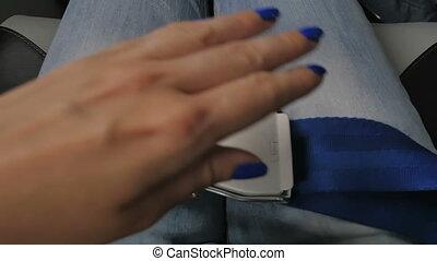 Seat belt in the airplane. Female hands unfasten the seat...