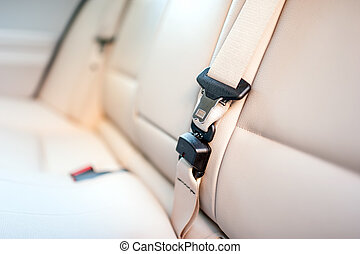 Seat belt on rear seat of modern car with beige leather interior