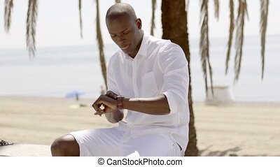 Seated black male model checking his watch besides palm tree...