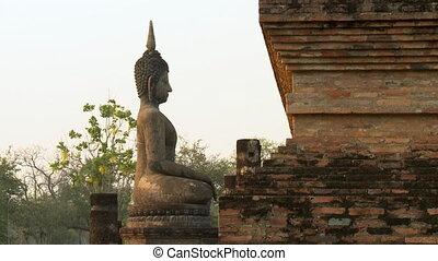 Seated Buddha image facing brick wall of temple