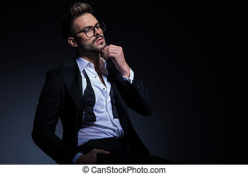 seated elegant man playing with his beard and looks away