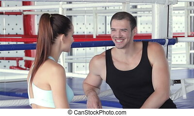 Seated fitness instructor and a young girl athlete discussing the program