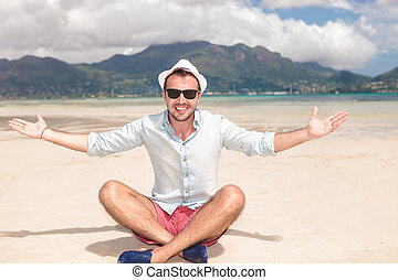 seated happy young man invites you to the beach