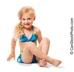 Seated little blond girl in swimsuit isolated on white background.