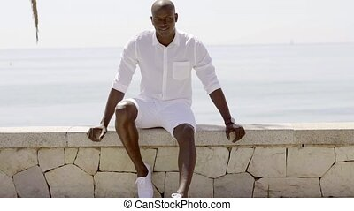 Seated male model wearing shorts and dress shirt while on...