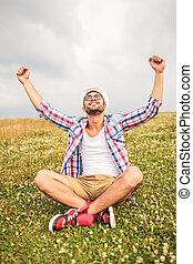 seated man celebrates success with hand in the air