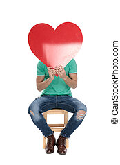 seated man hiding his face behind a big red heart