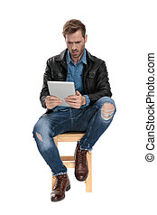 seated man holding a tablet scared