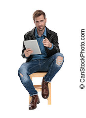 seated man with tablet pointing ahead
