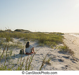 Seated Woman in the Beach Sand Dunes Faces a New Day