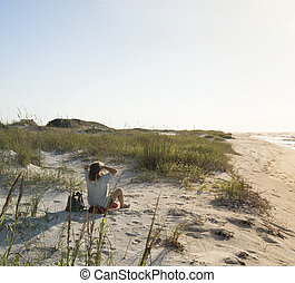 Seated Woman in the Beach Sand Dunes Greets the Rosy New Day