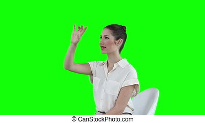 Seated woman scrolling through icons on a virtual touchscreen