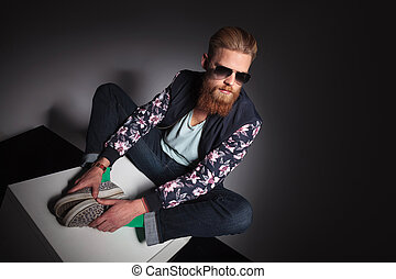 seated young bearded man looks away