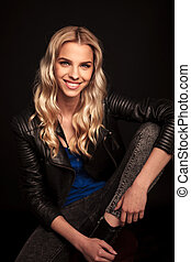 seated young blonde woman in leather jacket laughing