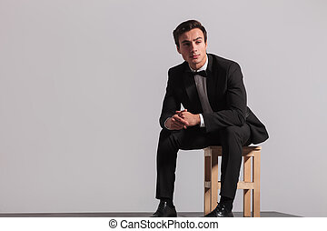 seated young businessman in tuxedo looking away