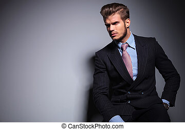 seated young fashion model in suit looks away - seated young...