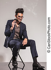 seated young man in suit smoking cigarette and looks down