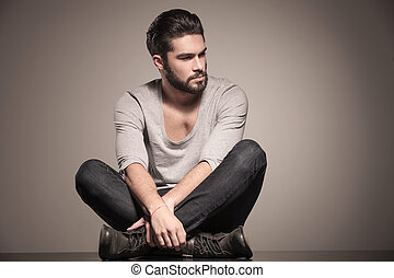 seated young man with beard looks away