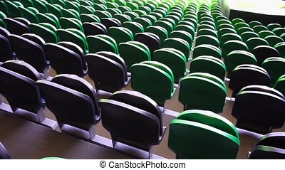Seating rows in a stadium with weathered chairs