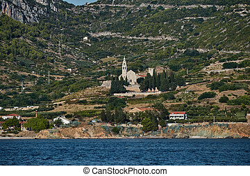 Seaview of the cathedral St.Nicholas in Komiza city at sunset - the one of numerous port towns in Croatia, mountain is on background