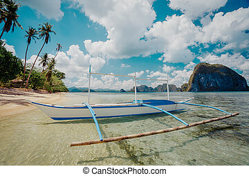 Seaview with traditional fishing boat on the beach under cloudy sky in El Nido. Palawan, Philippines