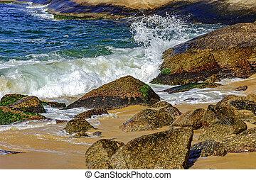 Seawater crashing on stones - Wave crashing on the rocks of...