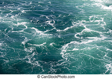 Turquoise green Seawater with sea foam as background
