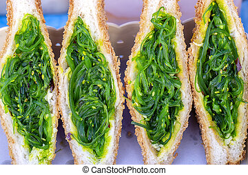 Seaweed salad sandwich for sell at street food market in Thailand, close up. Tasty green seaweed salad sandwich close up