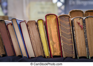 Second hand hardcover books leaning against each other for...
