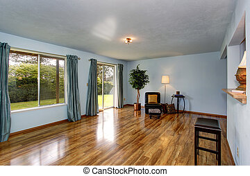 Secondary living room with blue interior and hardwood floor....