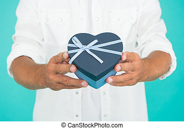 secret attraction. man hold heart gift box. present with love.