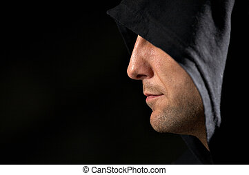 Secret - Profile of the man in a hood on a black background...