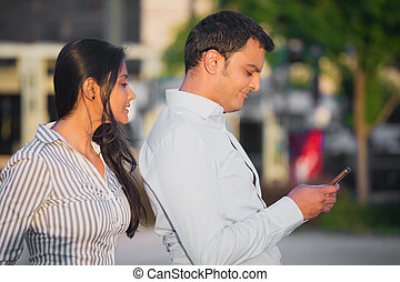 Secret texts - Closeup portrait, woman watching man over...
