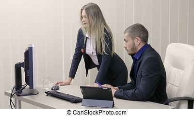 Secretary and her boss at the table next to a computer