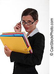 Secretary holding a binder and peering over her glasses